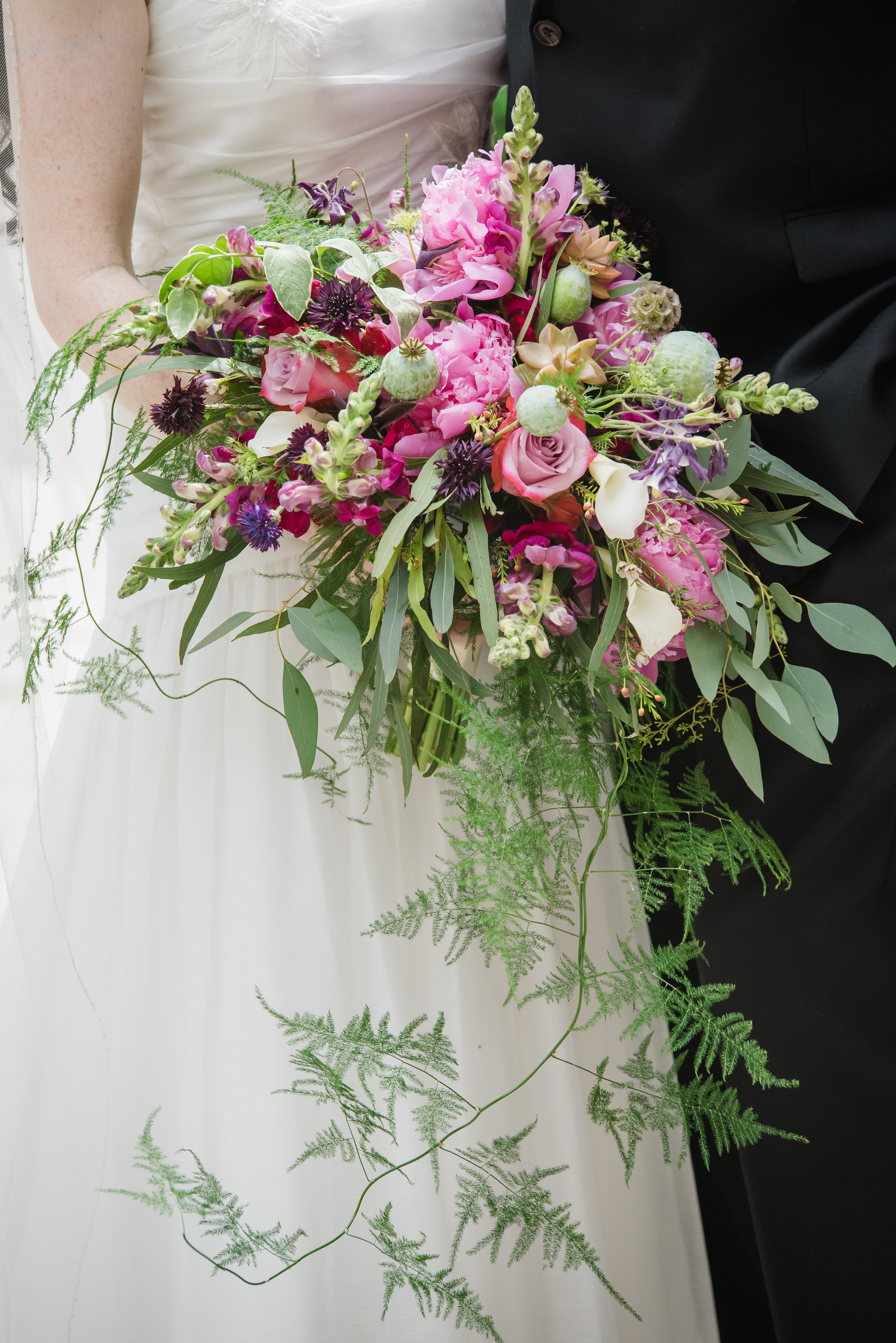 A beautiful, organic cascade with rich pinks and plums. Featuring Pink Peonies, Hot Pink Snapdragons, Pink Roses, and mixed Greens.  (Angelina Rose Photography)
