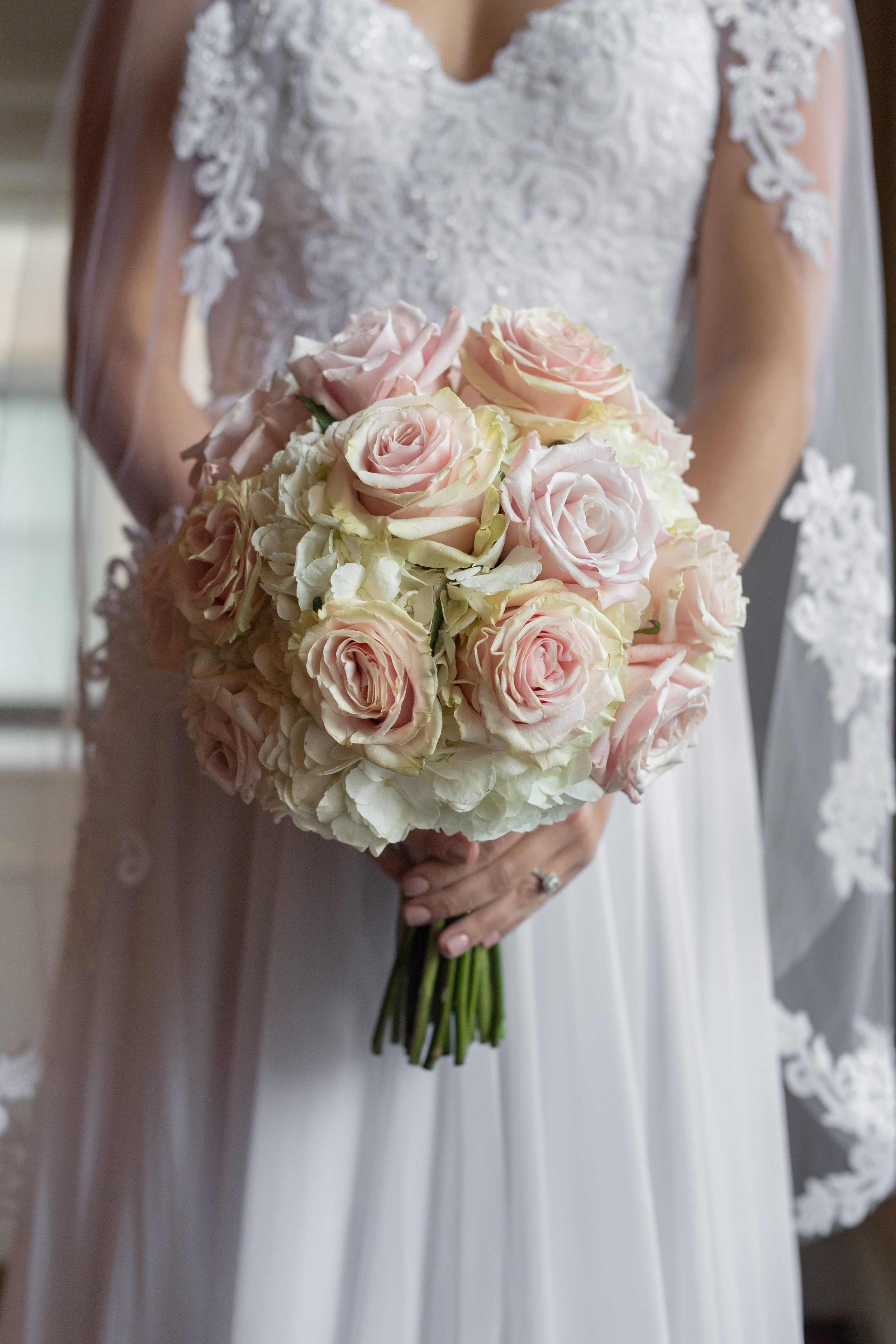 This elegant and romantic bridal bouquet is simple yet sweet. Pale Pink Roses and White Hydrangea balance a subtle color palette with a soft pink glow.  (Ned Jackson Photography)