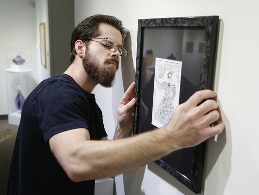 "Michael Crowthers carefully hangs a pen, ink and 23K gold work titled ""The Muse"" by artist Ilana Debikey Monday, December 14, 2015, at the Art Museum of Greater Lafayette. Crowthers is Curator of Collections Exhibitions and Education.(Photo: John Terhune/Journal & Courier)"