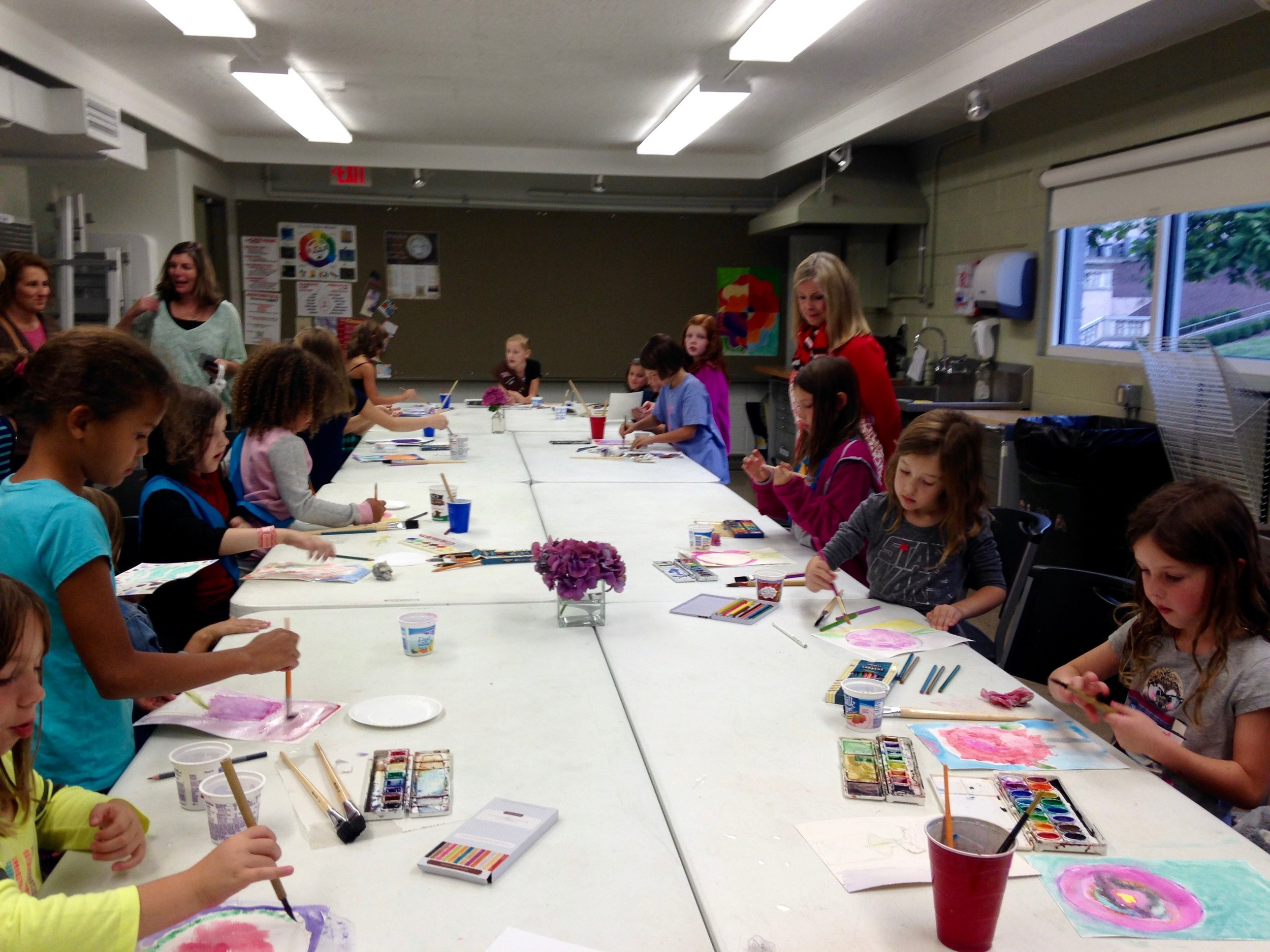 A brownie troupe visits the Art Museum.  After a docent led tour, they are engaged in a painting project.