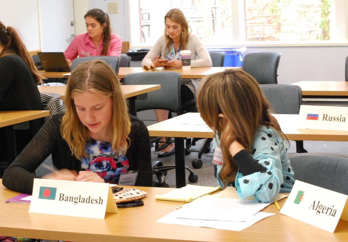 Audrey Hankins (left) and Bethany Blakeman (right), representing Bangladesh in the General Assembly, collaborate on a proposal to address the effect of forced migration caused by climate change.