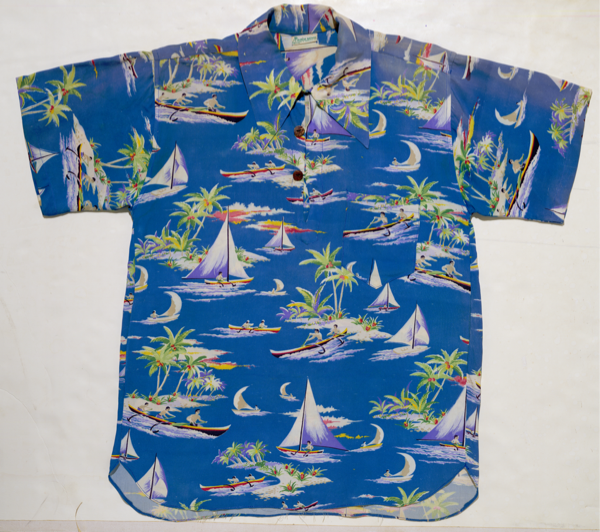 The there-button pullover shirt was the predecessor to the more relaxed, open-front Aloha shirt. With whimsical outrigger canoes frolicking around a tropical island, this was an early example of a Hawaiian-inspired print.