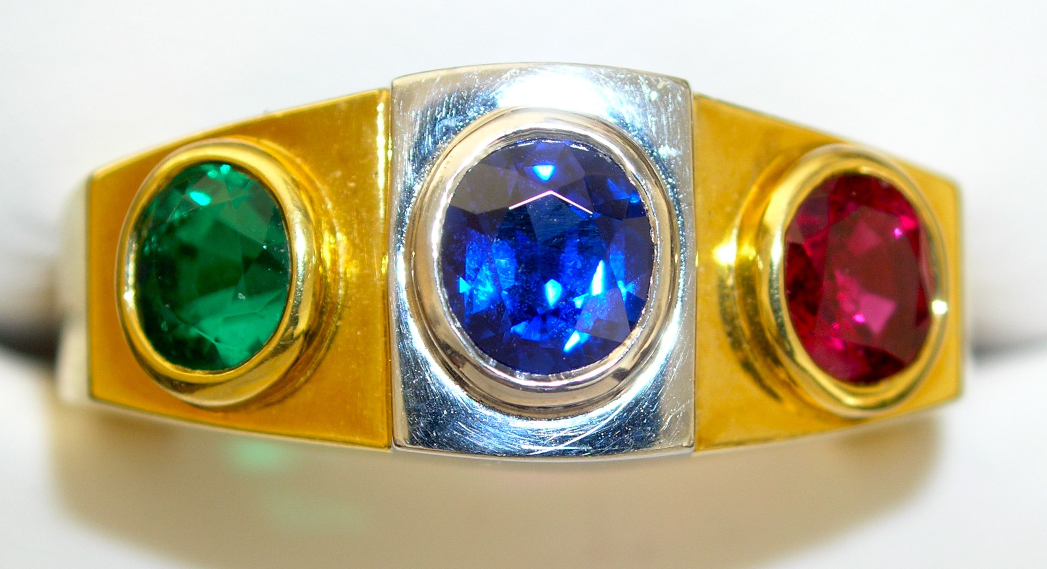 """The late master cutter & gem trader Reginald Miller wore this """"trip ring"""" to serve as his color guide on his trips to the world's gem producing capitals from 1951-1988. This Colombian emerald, Burma sapphire, and Burma ruby served as his benchmark for the finest."""