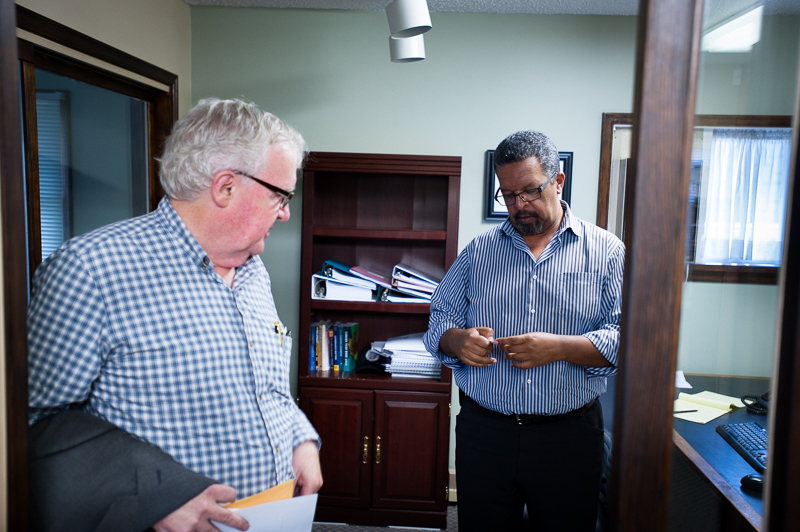 David McKenzie and Aklilu Mulat, the executive director at HOPE International Development Agency, study my business card. Aklilu came to study in Canada from Ethiopia in 1979, only 17 years old. Now, a seasoned Canadian, he reaches out across nations to help people in Ethiopia and all over the world. At HOPE International office, New Westminster, BC, Canada on August-15-2013. Photo: Art Zaratsyan