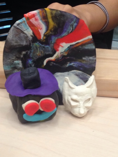 Here's a picture of Rochely's hand holding up Play-doh sculptures. The colors represent different values that one must uphold as members of the North Philadelphia Youth Advisory Council. Rochely's sculpture is the fore fronting, cube-shaped face. To Rochely, respect (represented by the color black), is the most important quality to exchange with one another as a successful Council.