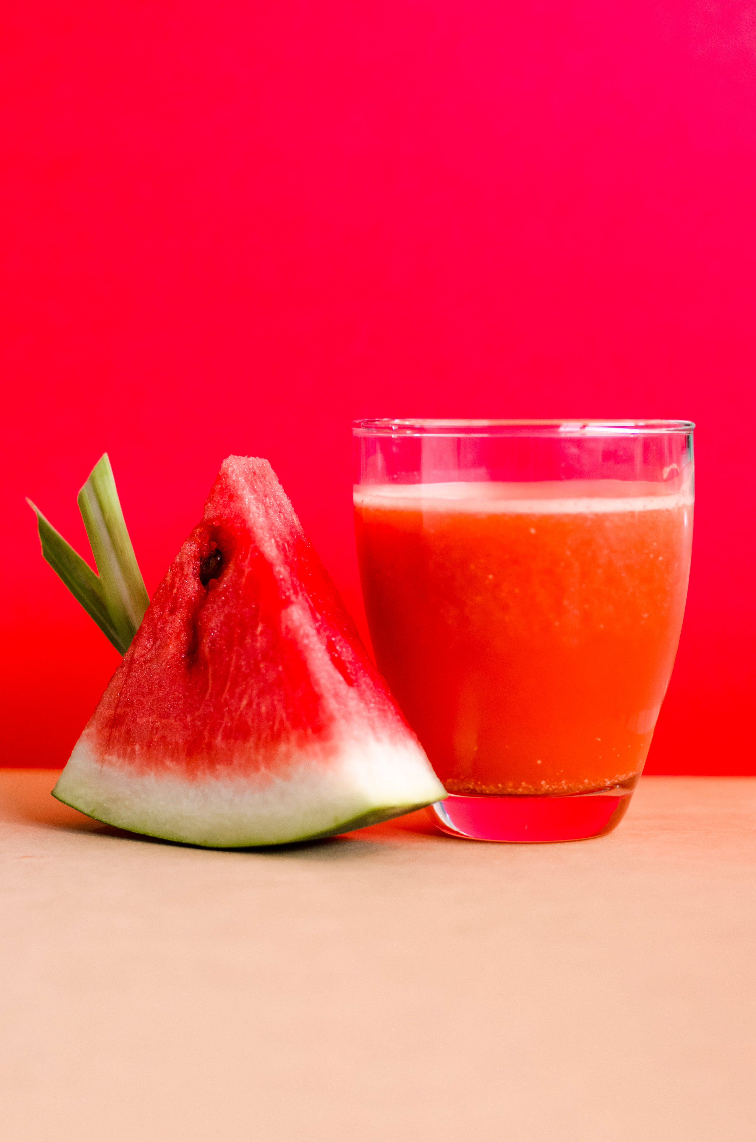 Canva - Watermelon Shake Filled Glass Cup Beside Sliced Watermelon Fruit on Brown Surface.jpg