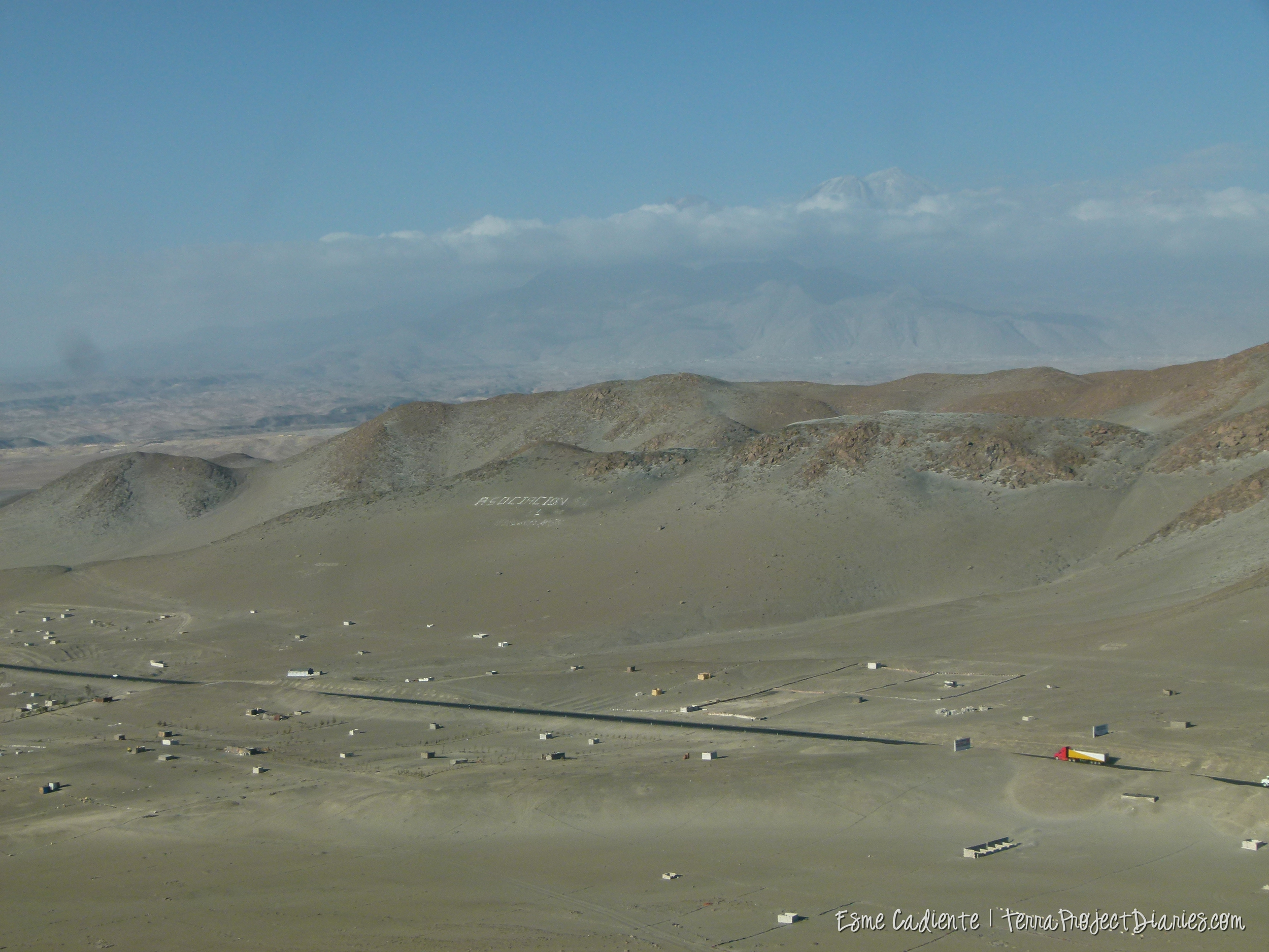 A strip of highway, accompanied by shacks here and there, slice through the desert in Southern Perú.