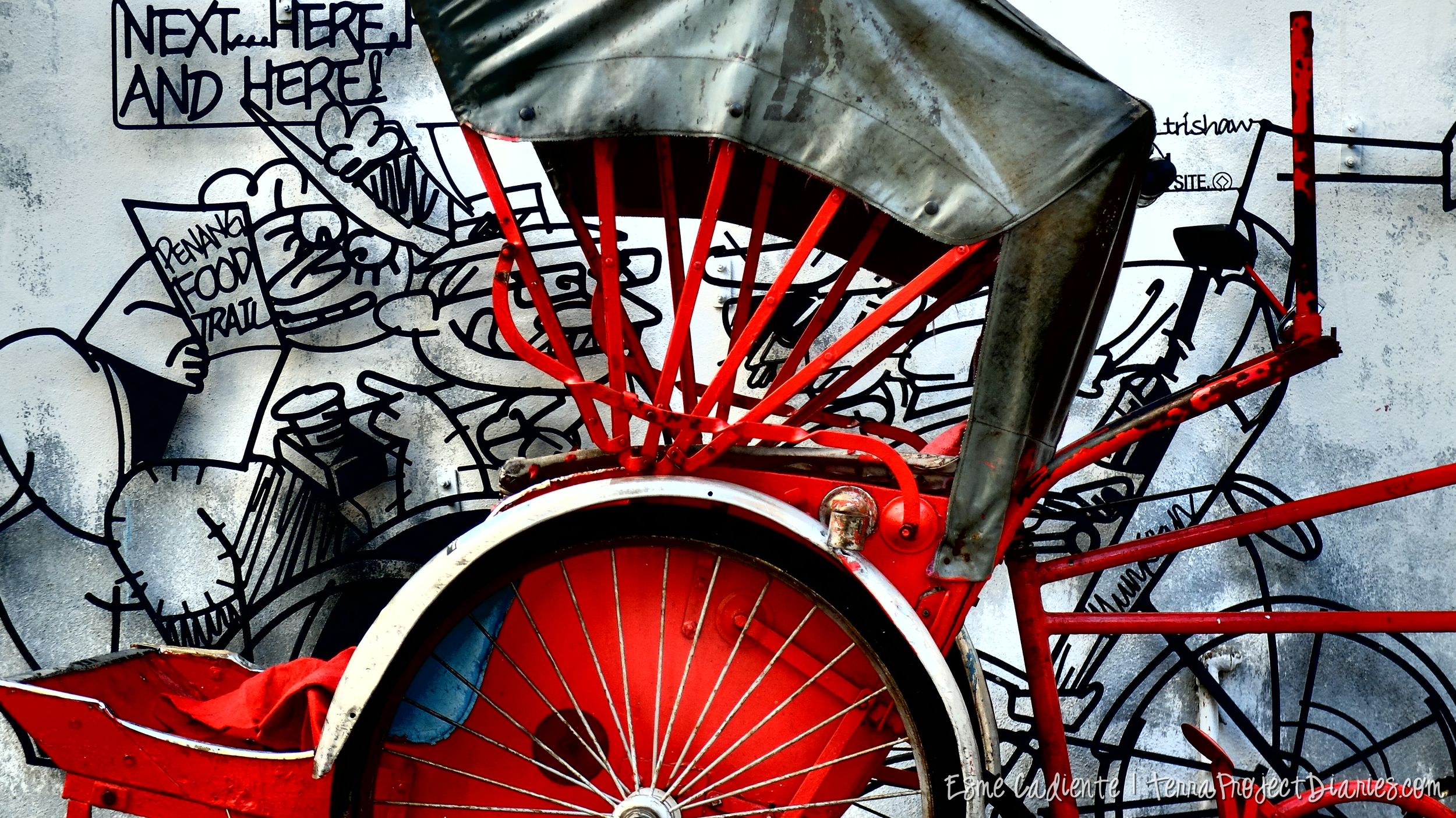 Trishaw stationed in front of an iron street art piece along the Penang Food Trail, Georgetown.