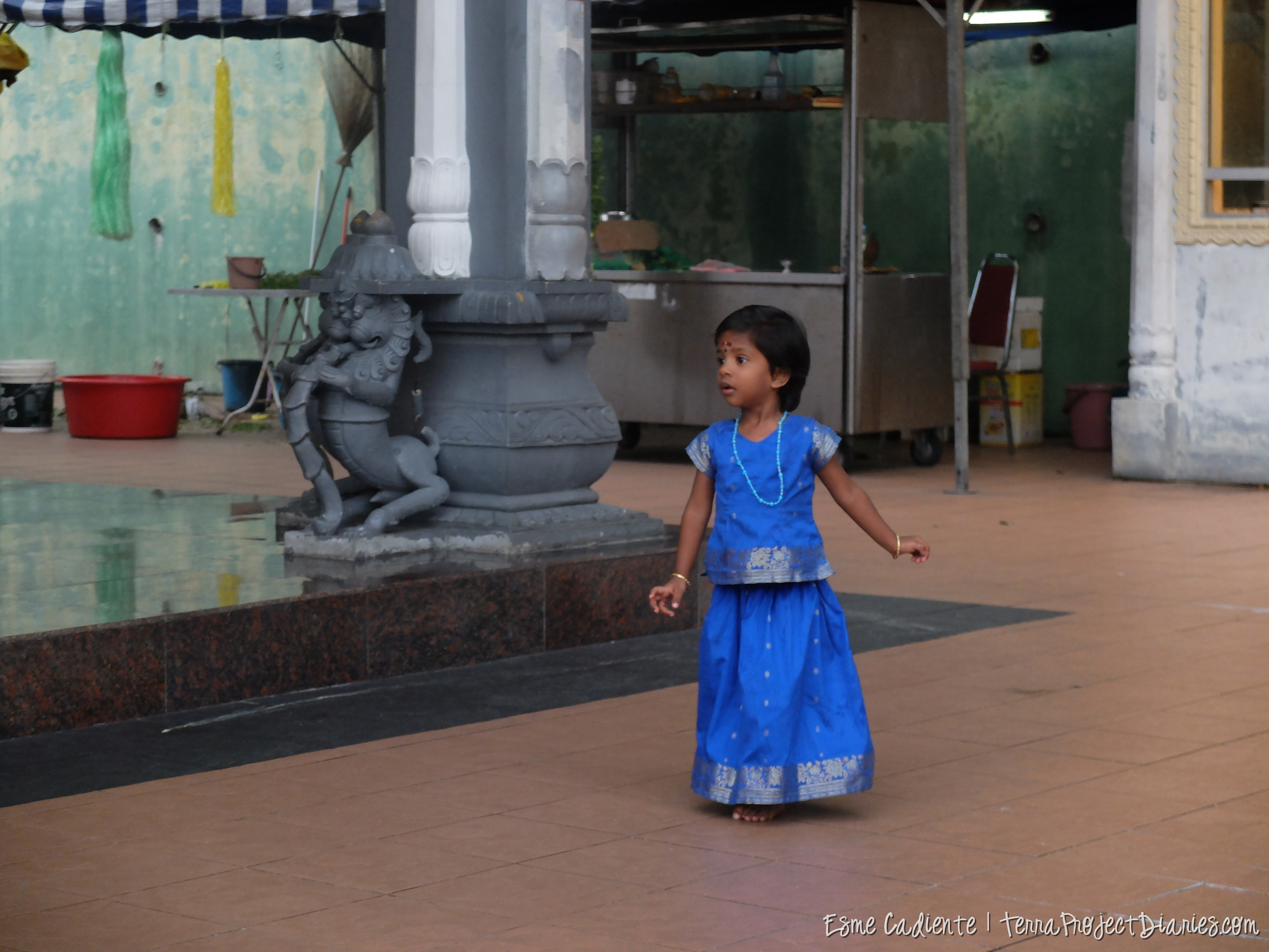 An Indian child runs around an Indian temple