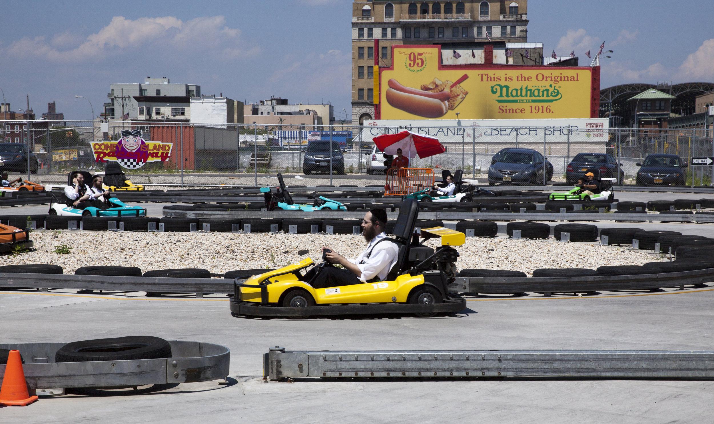 CITY LIFE: Four Hasidim enjoy a summer zip around the go-cart track at Coney Island - Brooklyn, New York