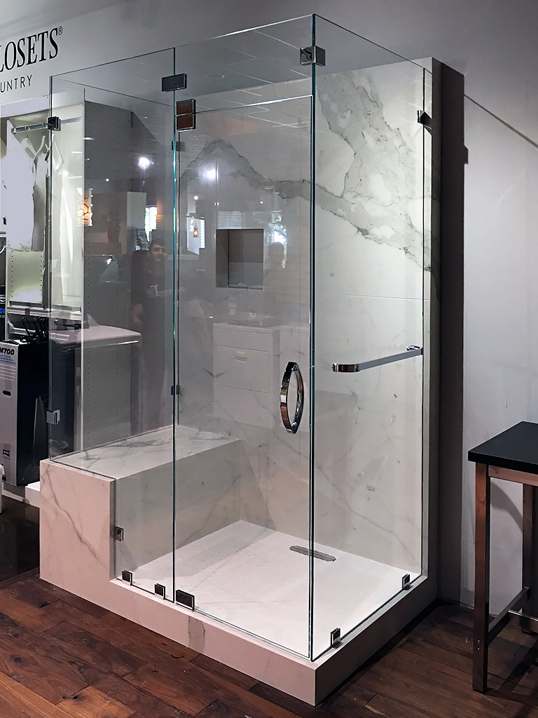 This notched, double 90-degree frameless enclosure by Shower Doors of Austin features low-iron glass, chrome hardware, and a transom. It can be seen at  The Frog Pad designer showcase  in Lakeway, Texas.