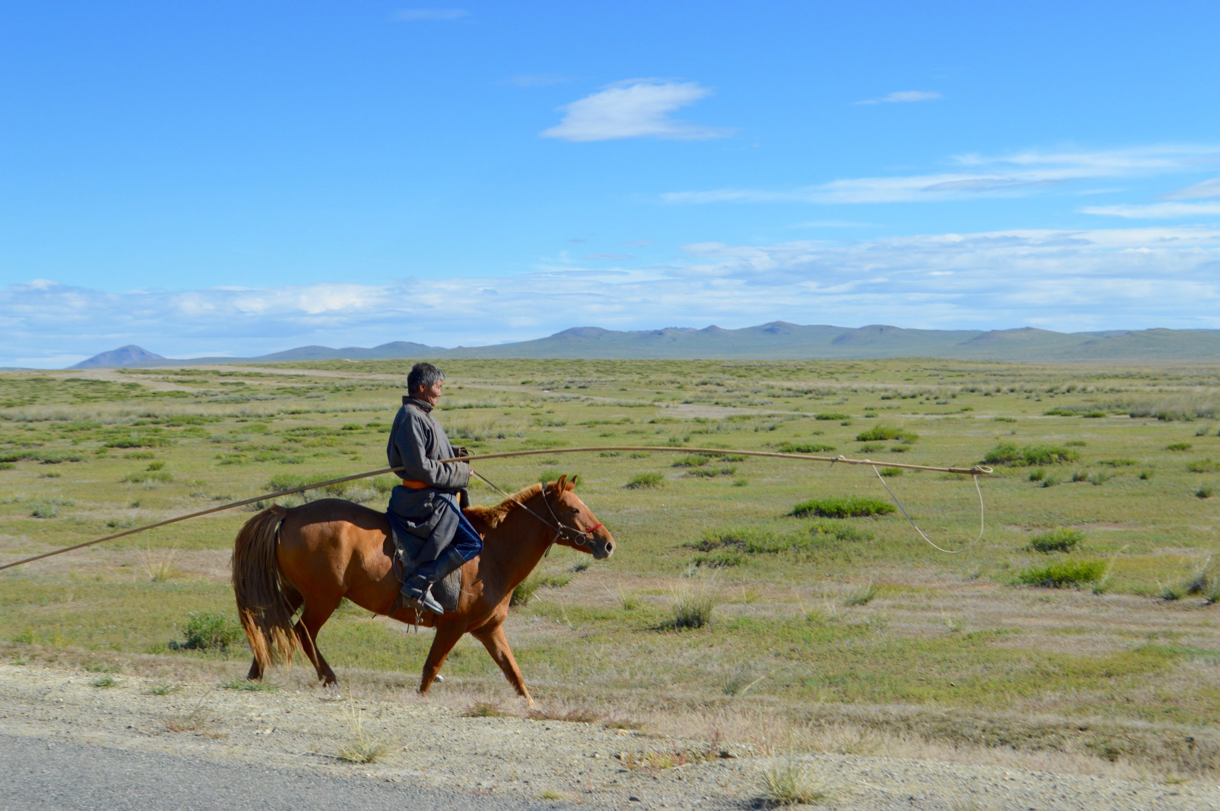 A Mongolian herdsman in traditional clothing on horseback
