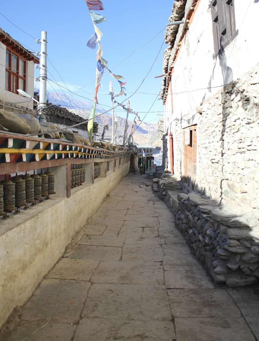 A Kagbeni Street complete with prayer wheels, flags and mountains beyond. Photograph © Claire Orrell 2014