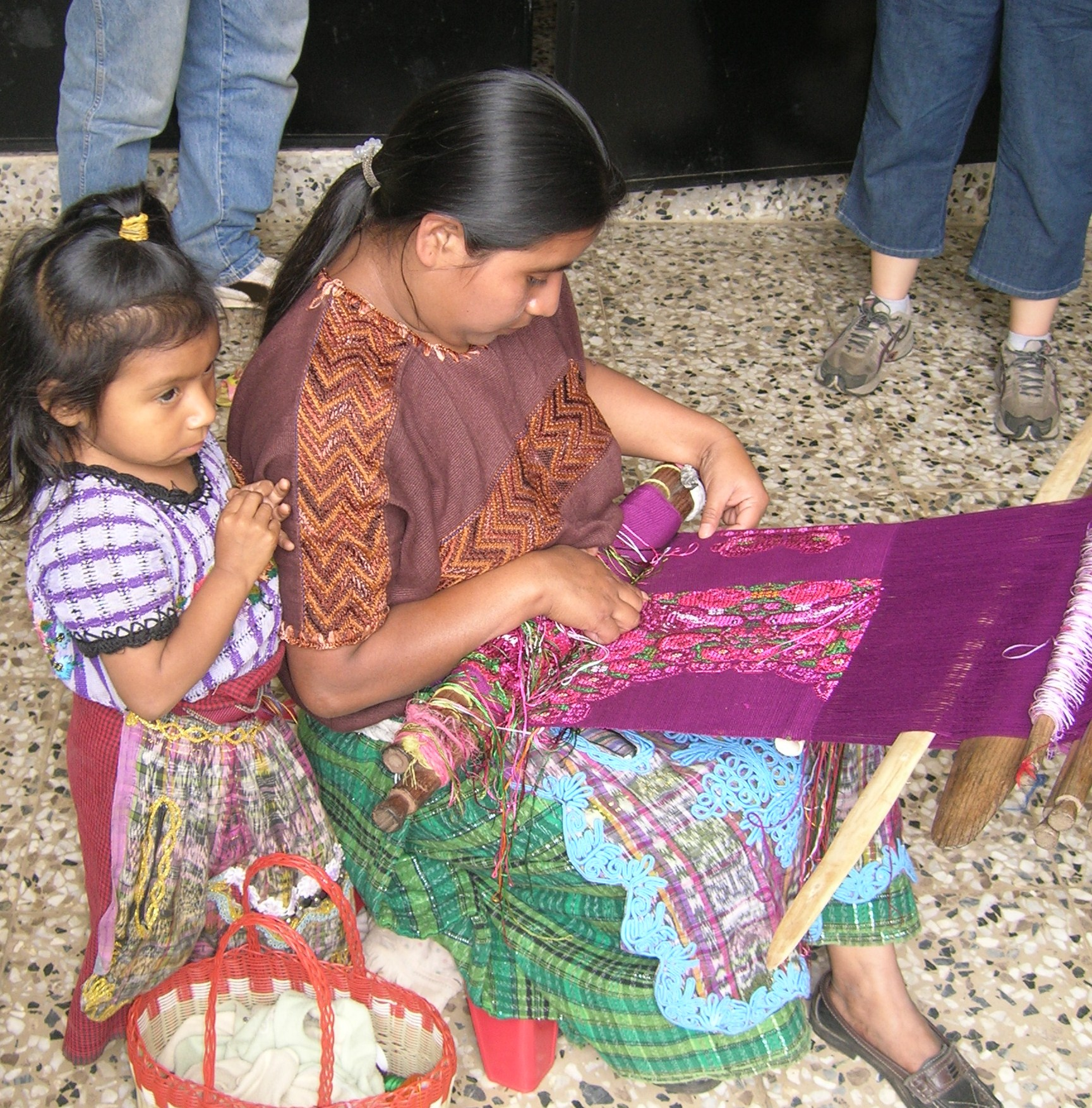 A Mayan weaver with her daughter. Backstrap weaving is a part of the culture of the western highlands of Guatemala. Young girls begin learning how to weave at about 7 years of age.