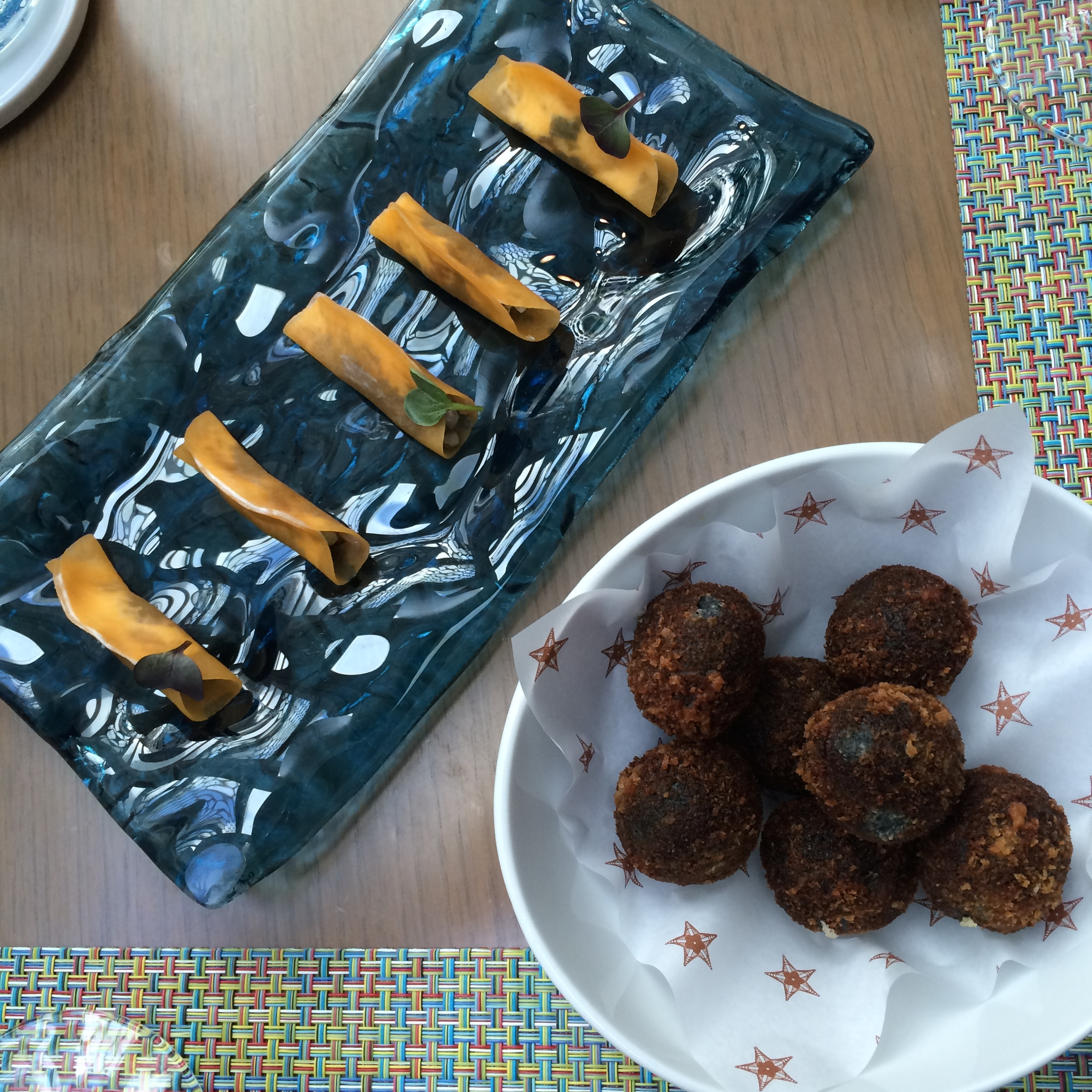 Delicious Squic ink croquettes and pumpkin ravioli with marinated anchovies