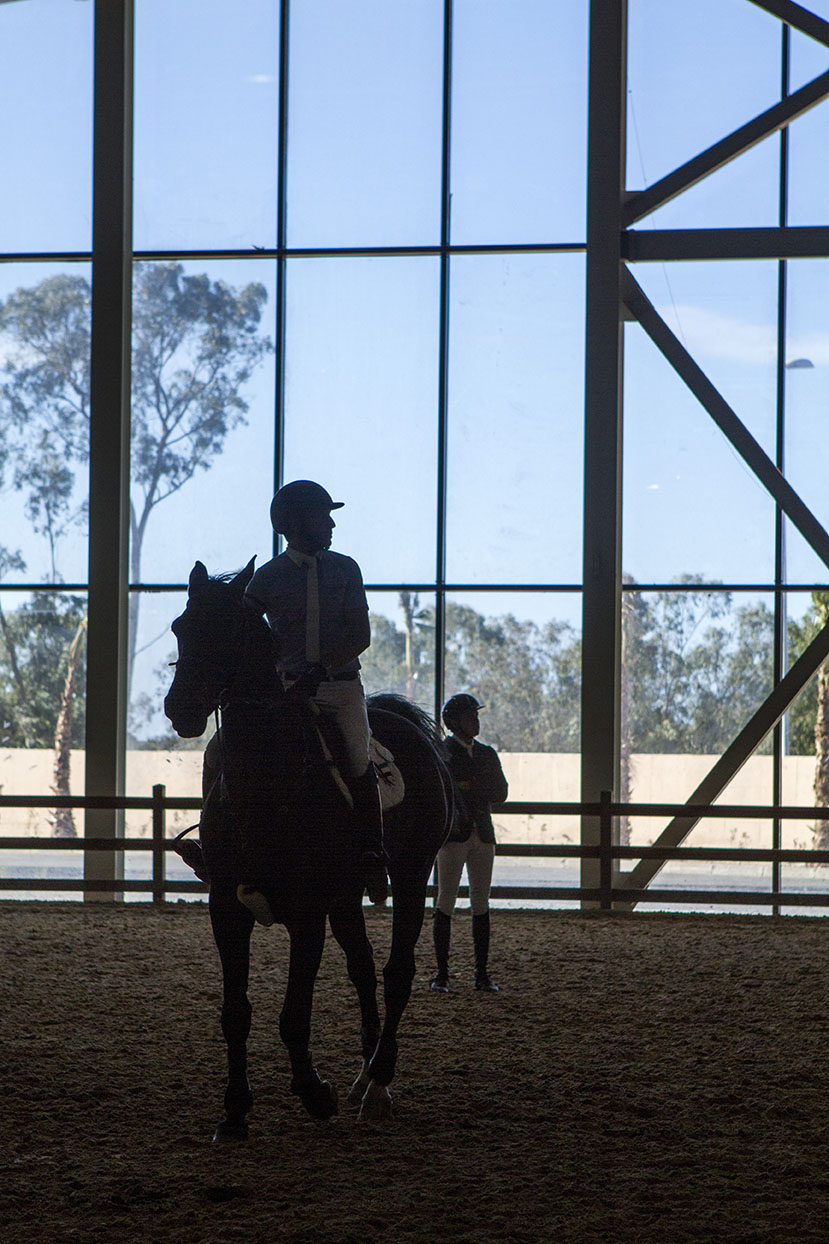 A HORSE RIDER LOOKING AT THE SCREEN IN THE WARM UP SECTION TO SEE THE RESULTS OF HIS COMPETITOR