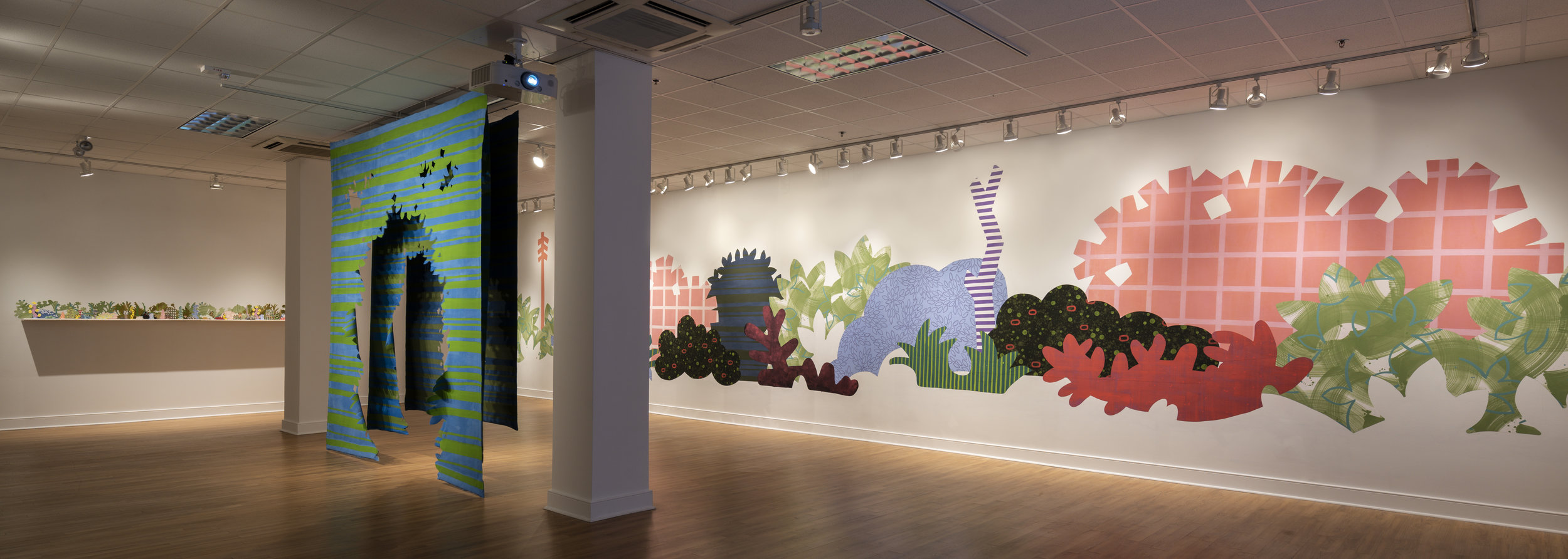 From right to left:     Piecemeal Promenade   (2019) 48ft x 11ft; latex on muslin cut-outs, adhered to wall;     Proscenium Hedgerow   (2018) 11ft x 10ft x 2ft; series of three latex on cut muslin panels;    Horizon Allsorts  , (2018) 12ft x 1ft; (6) floating wood shelves, painted muslin, ceramic, underglaze and glaze