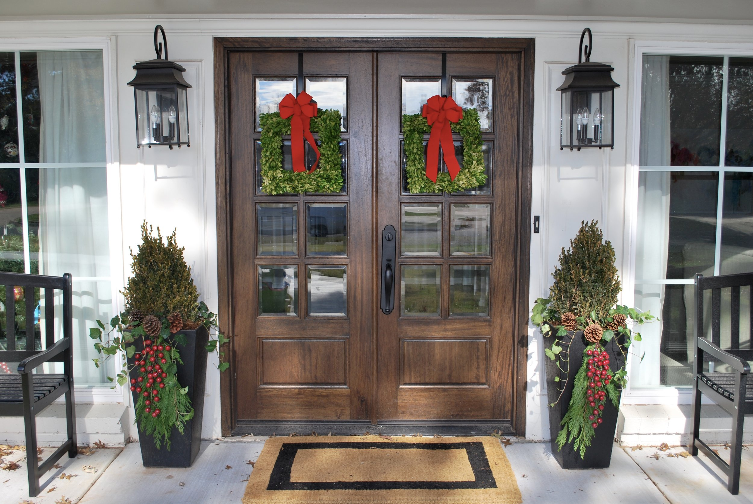Holiday Planter Bling   These last few weeks the Adorn elves have been busy spreading holiday cheer to front porches and store fronts all over KC and OKC. We are in the holiday spirit and wanted to share some of our favorite decorating ideas with you to get your outdoor planters ready for the season.  In the picture above we started with a boxwood in each planter and then added festive holiday décor to create our finished look. Our go-to holiday décor for pots is red berries, pine cones and fresh greenery…it's looking pretty festive right? Round gold and silver ornaments in various sizes and textures are also a fun addition to planters if you want a more elegant look. If you have a wreath or other door decoration you can use coordinating decor as filler in your pots to tie it all together for a cohesive holiday look.  We love fresh evergreen garland! It smells SO good and is SO lush! One of our favorite things is to encircle the top of a planter with it. Word of warning though if using fresh greenery, the downside is that it dries out over time. We recommend spraying the greens with an anti-desiccant product like Wilt-Pruf so the needles will stay on longer and spraying the greenery with water 3 times a week so it stays fresh. It's so beautiful and festive, it's worth the extra effort to keep it pretty, trust us!