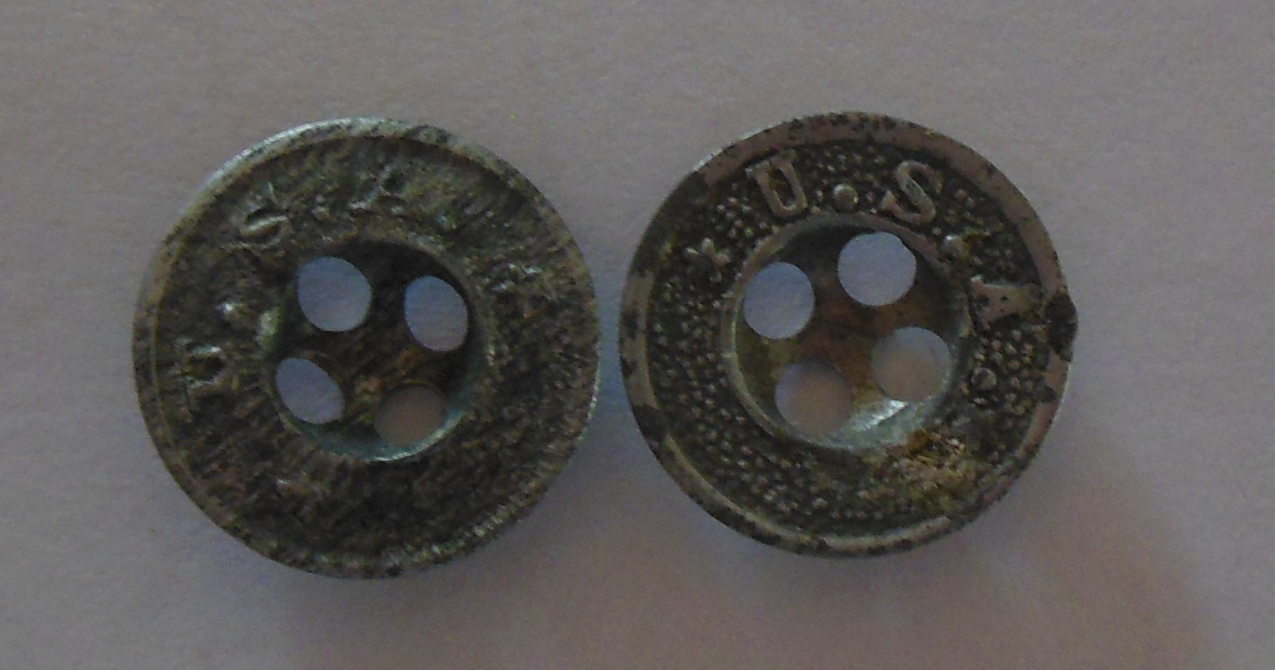 World War I era Pant buttons. It looks like these two had some hard use.