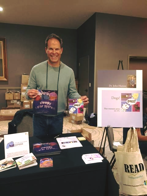 "Founder Dr. John Hutton with two of his own blue manatee press titles, ""Sleepy Solar System"" and ""Dogs!"""
