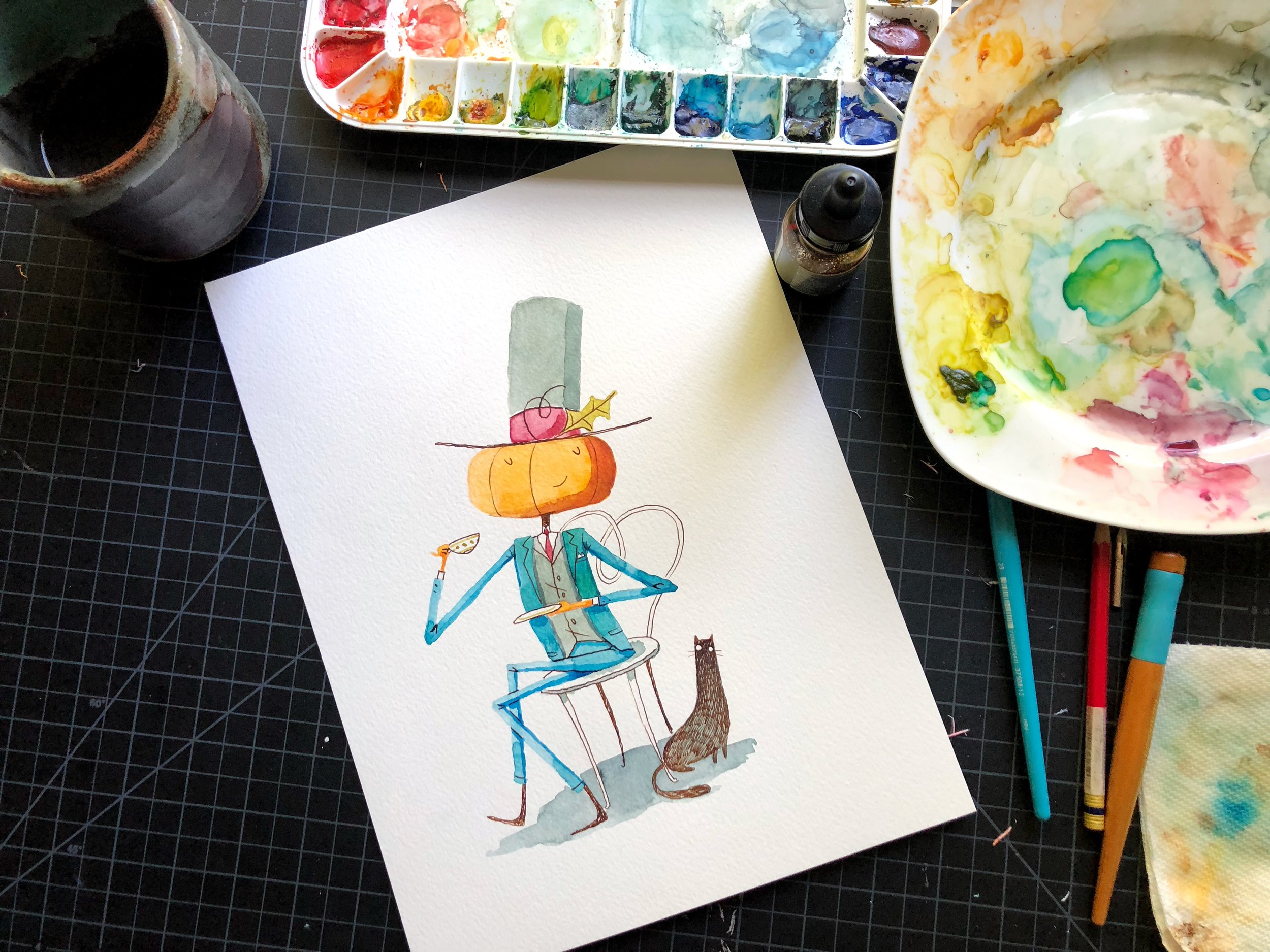 After the initial Inktober sketch, Erin refined Mr. Pumpkin's look and made him kid-friendly for the picture book, seen here in her studio.