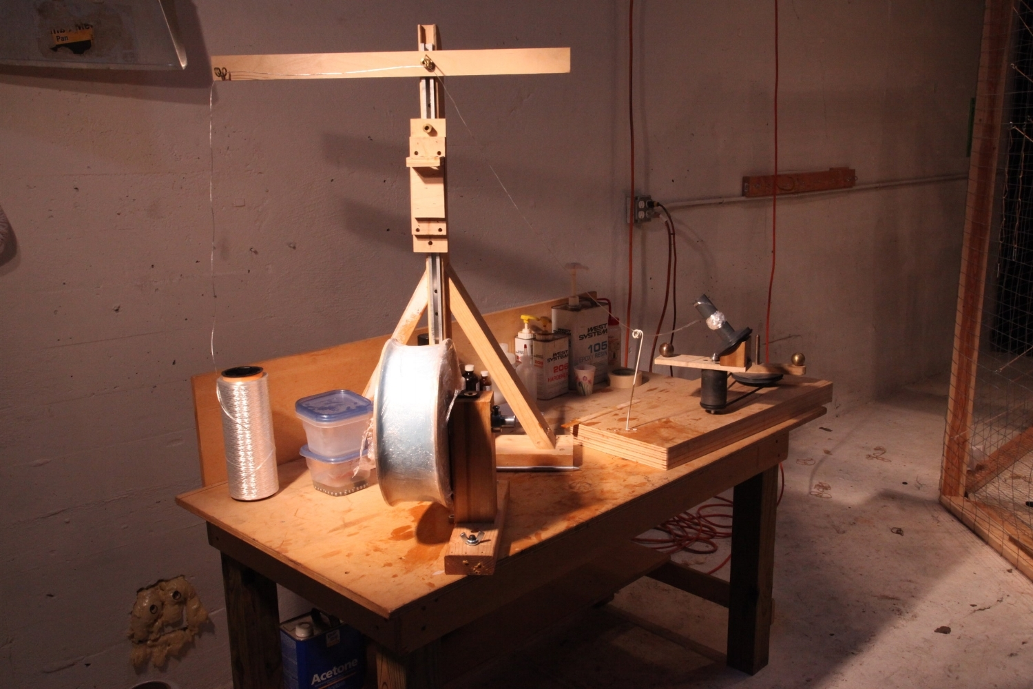 """Fiberglass thread (""""tow"""") is drawn through epoxy resin and wound upon an uptake wheel at the resin ball winder table."""