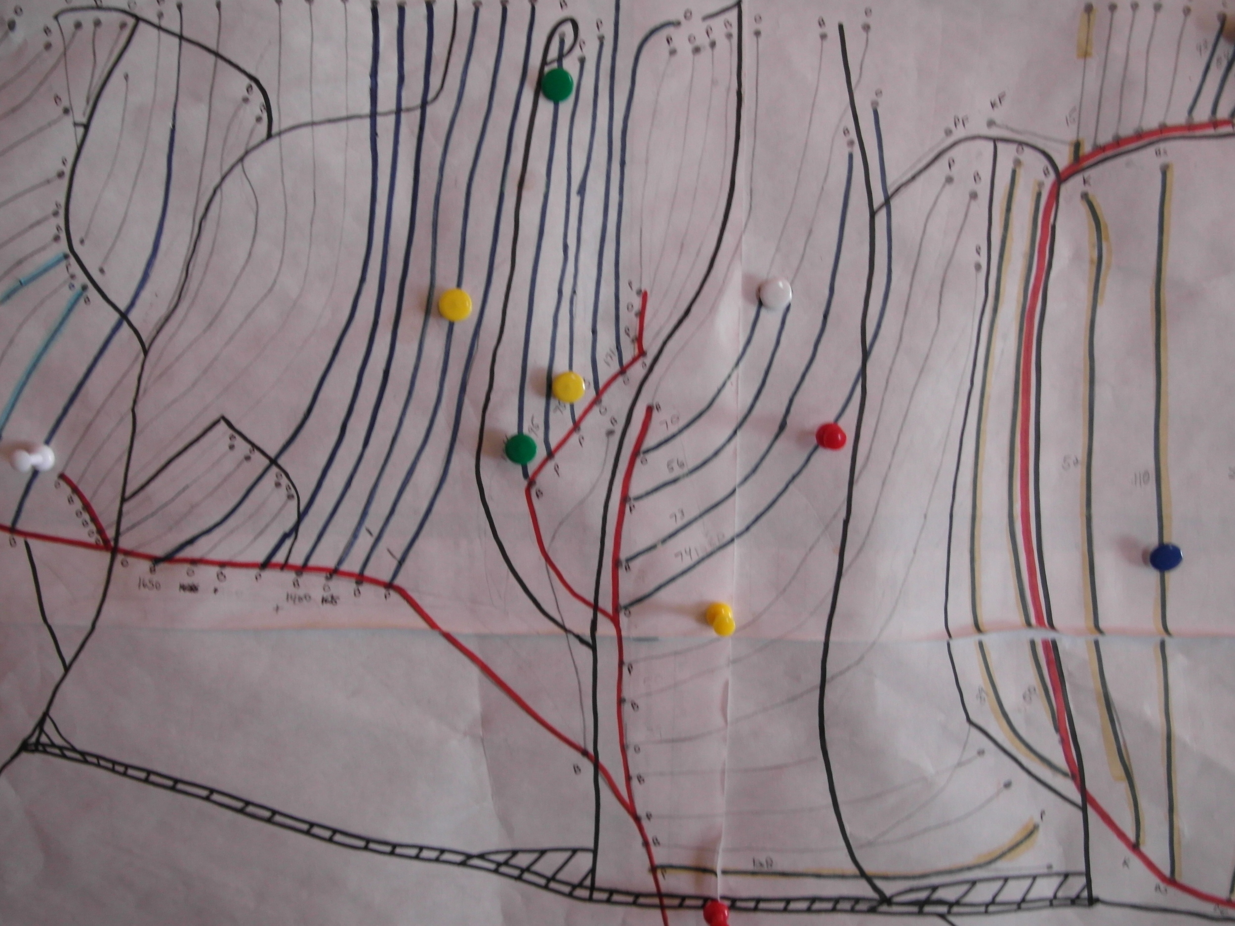 A hand-drawn map of our sugarbush, with finished lines shown in blue.  Pins show areas where lines need to be repaired.