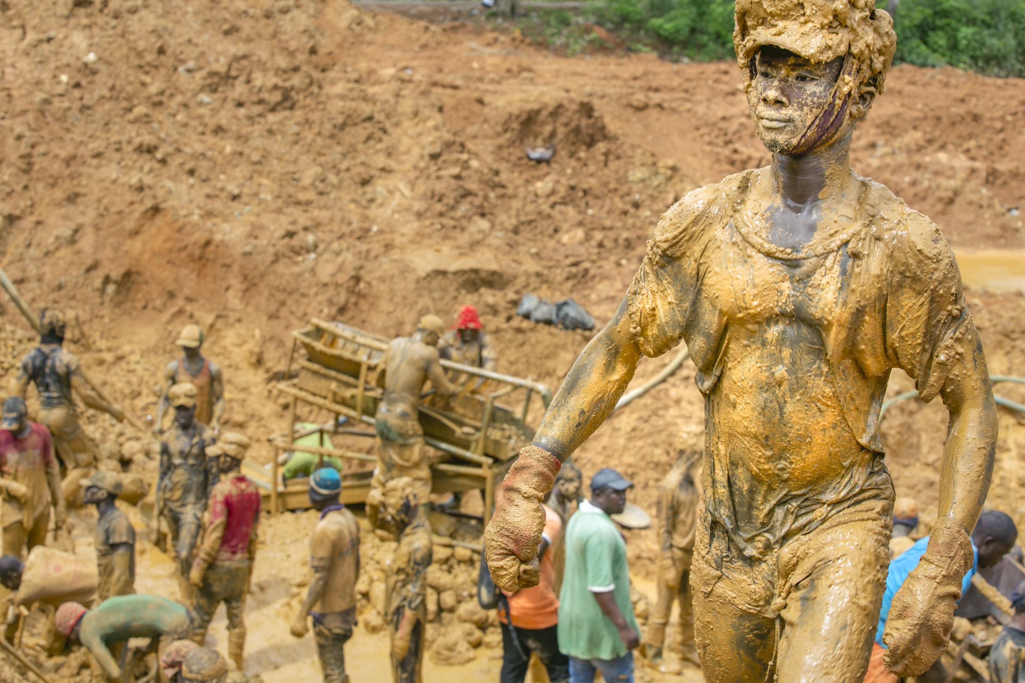 A young miner emerges from a pit covered in mud. His job is to carry buckets of placer deposit (which contains the gold ore) from the sifting machine out of the pit to be washed and mixed with mercury to extract the gold.
