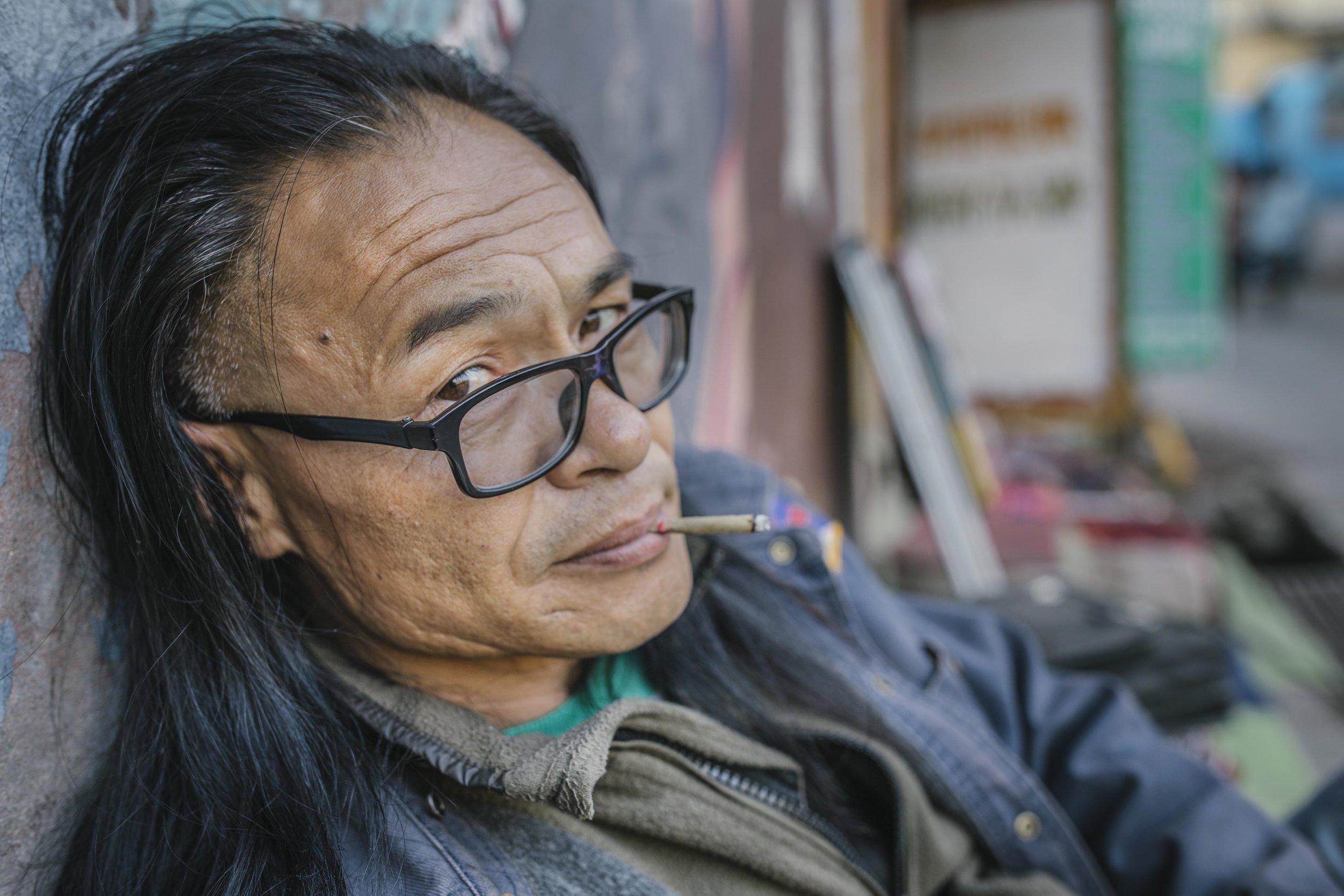 Mesib Norbu, former monk, writer and part of Free Tibet movement outside the poetry tea shop he runs in Mcleod Ganj, Himachal Pradesh, India.
