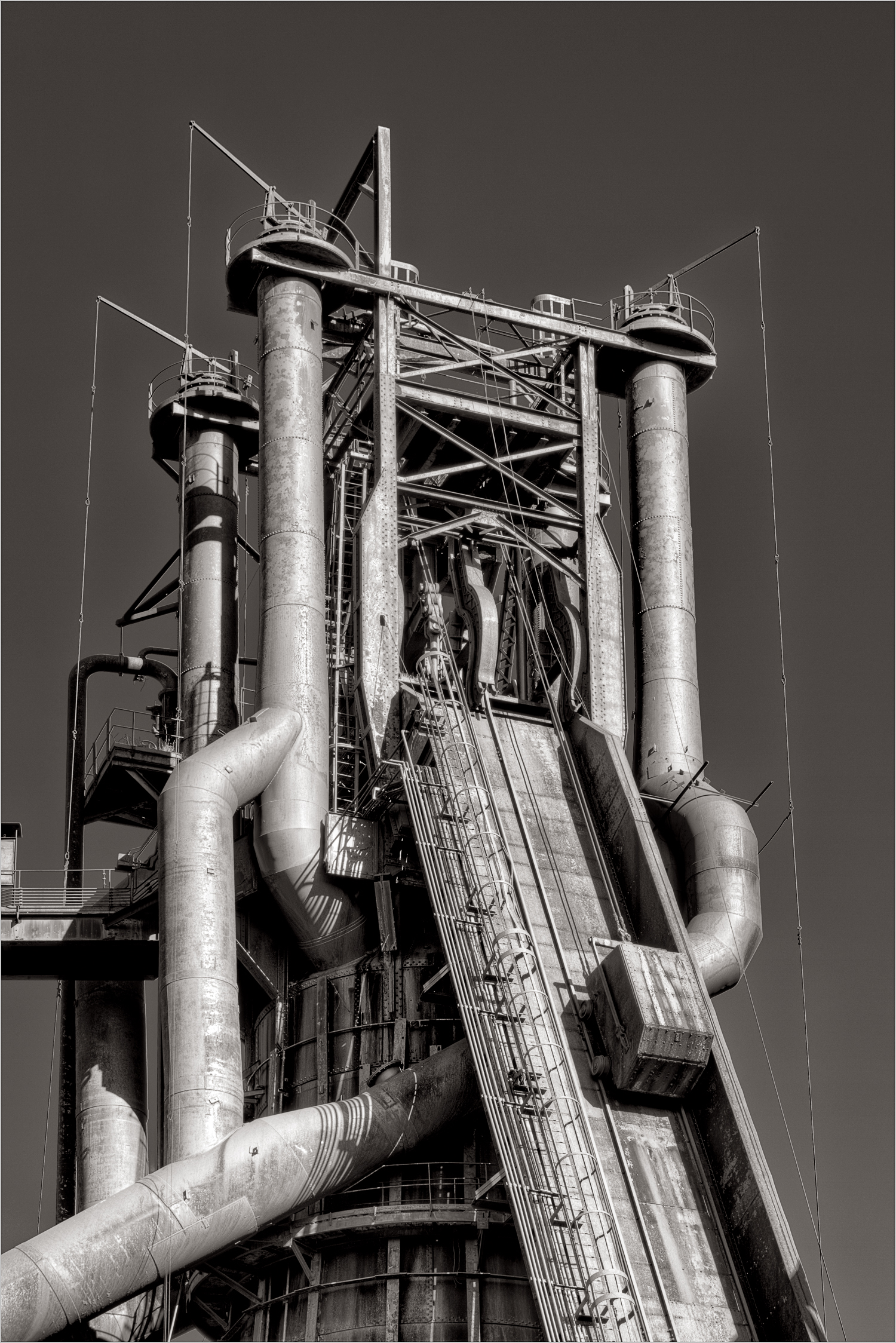 A skip cars ascends the Carrie Furnace. These cars were used to dump raw materials into the top of the furnace. The four large vertical pipes are bleeder valves, used to adjust the pressure in the furnace.