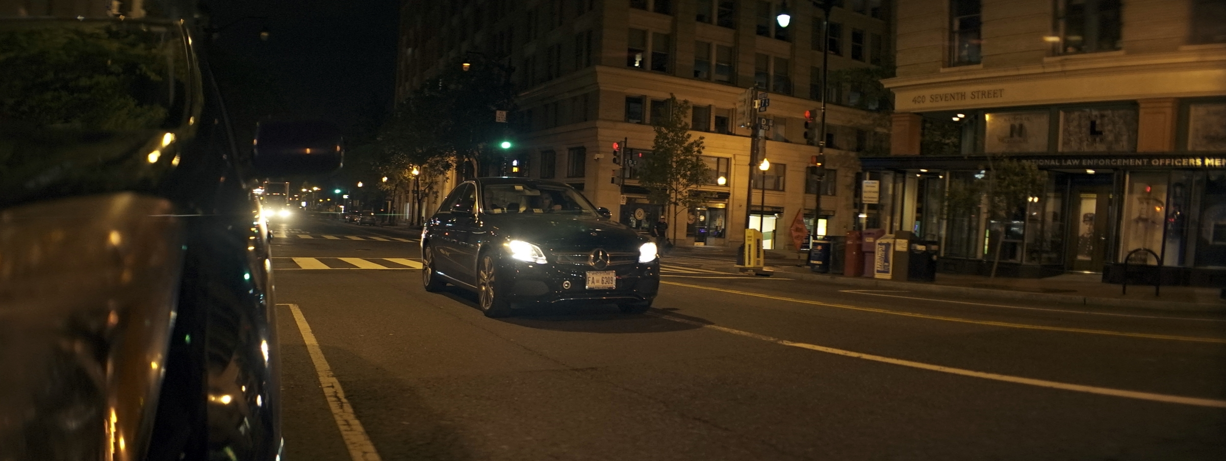 Elite 24.5mm anamorphic | Washington D.C. - A subtle flare can be seen here along the left third of the frame, triggered by a truck approximately 500ft down the street. Notice no flare from the headlights of the Mercedes because it is not on axis with the lens. Notice also the small green flare produced by the trafic signal above the Mercedes. Image captured wide open at T2.1. Photo by Keith Nickoson.