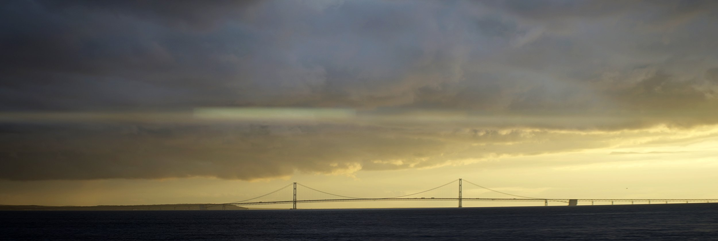 Lomo 100mm anamorphic lens | A subtle streak can be seen through the center of this picture of the Mackinac Bridge in Michigan. The sun was just out of frame right, about fifteen minutes before sunset. Photo by: Keith Nickoson