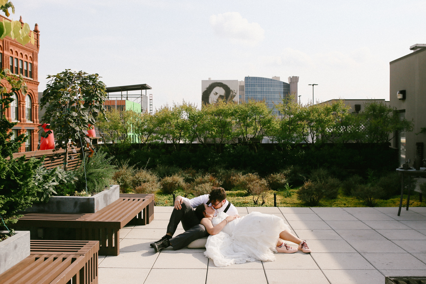 "Oh I was so excited to shoot a wedding at the Louisville 21C Museum rooftop, and it did not disappoint. I love art and rooftops and cityscapes and these two lovebirds. We found ourselves waiting a couple minutes for something so I cleared out the patio furniture and asked them to lay on the ground. They didn't hesitate and just like that, I got one of my favorite portraits. Now once you meet me, you'll learn I typically hate shots of people laying on the ground or in grass. It's just not natural and doesn't seem ""photo-journalistic."" But occasionally I make an exception in my head."