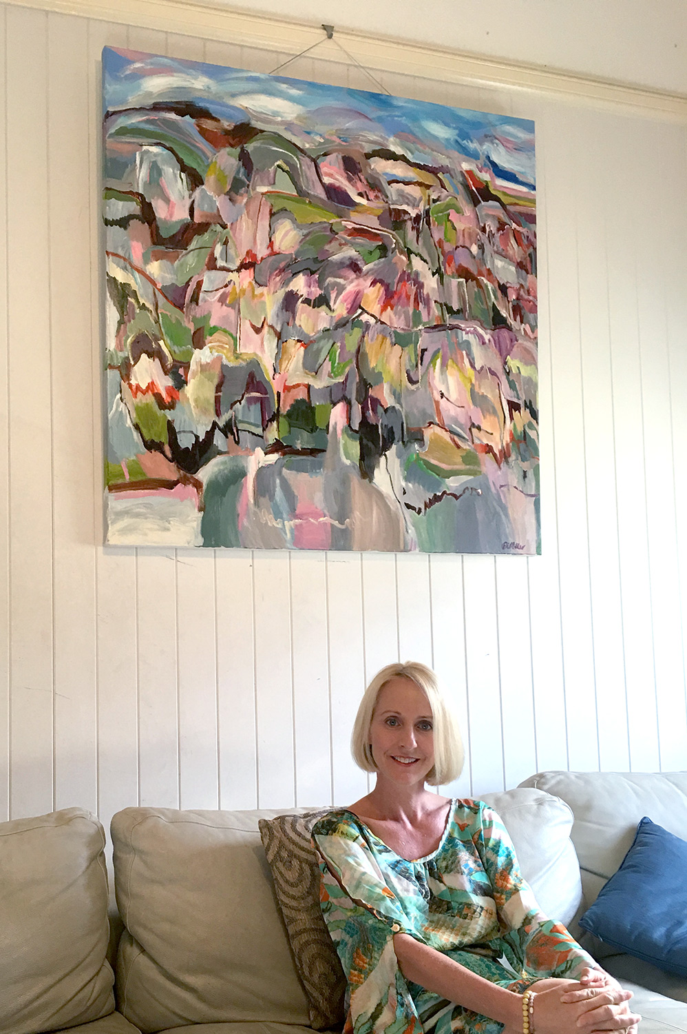Alison in her West End home in Brisbane with her commissioned abstract landscape painting