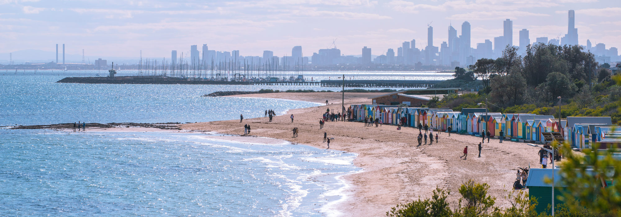 View looking North toward the City of Melbourne with Middle Brighton Pier and Bathing Boxes on Dendy Street Beach in the foreground.