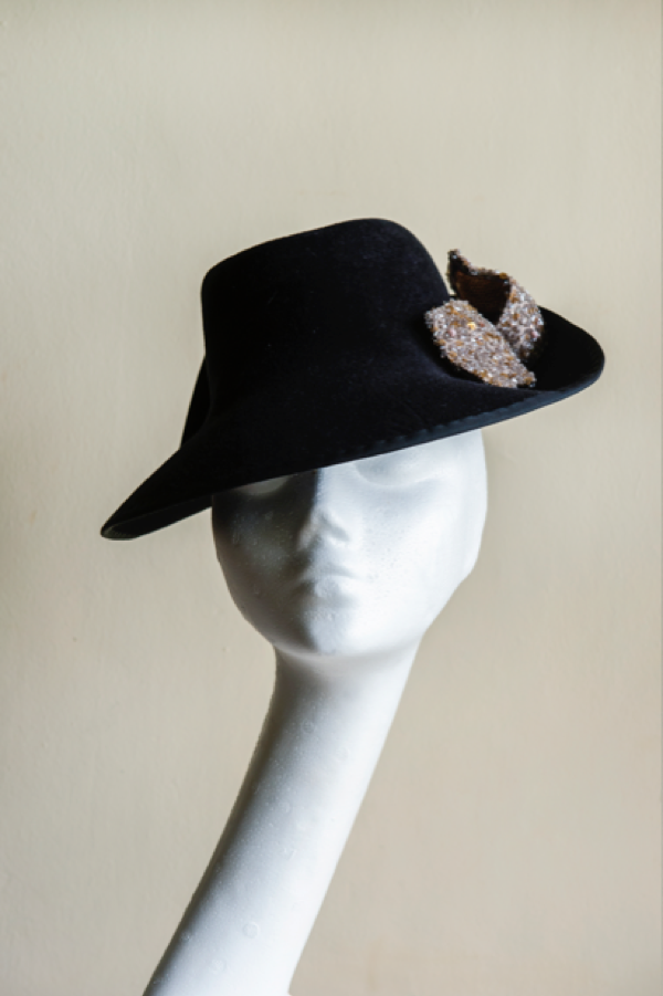 Black peachbloom felt percher hat   with a silk bow trim, which provides some unexpected sparkle. This hat is secured to the head with an elastic.