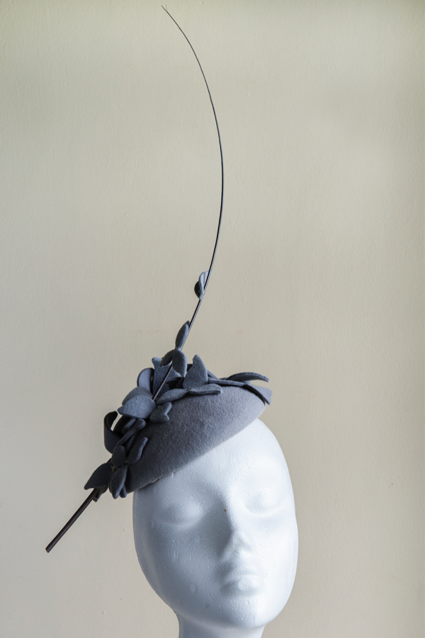 Grey peachbloom felt button hat   Trimmed with hand-beaded felt flowers and a quill. Easy to wear shape perfect for any winter occasions. This hat is secured to the head with an elastic.