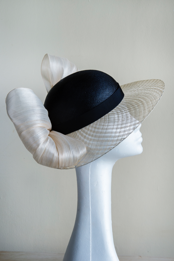 Dior brim hat with bow   An elegant hat, with a window pane sinamay brim, trimmed a big silk abaca bow. A classic, easy to wear shape made to the stand head it of 22.5""