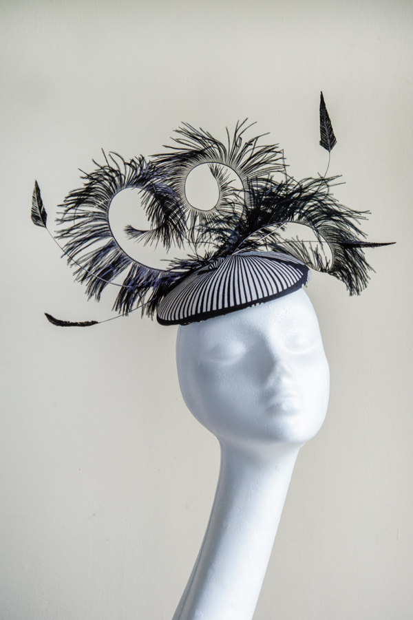 Fabric button hat   A playful button hat trimmed with loose ostrich feathers. Perfect for weddings. This hat is secured to the head with an elastic.
