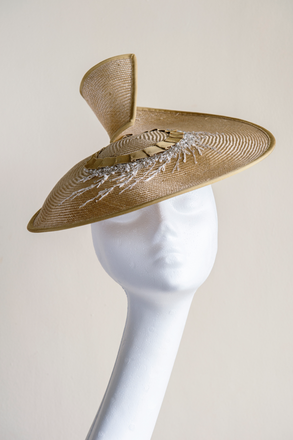 "Gold straw coolie hat with bead embellishment   A modern take on the ""coolie"" hat, a golden straw hat with hand-beaded embellishment in silver, white and gold. This hat is secured to the head with an elastic."
