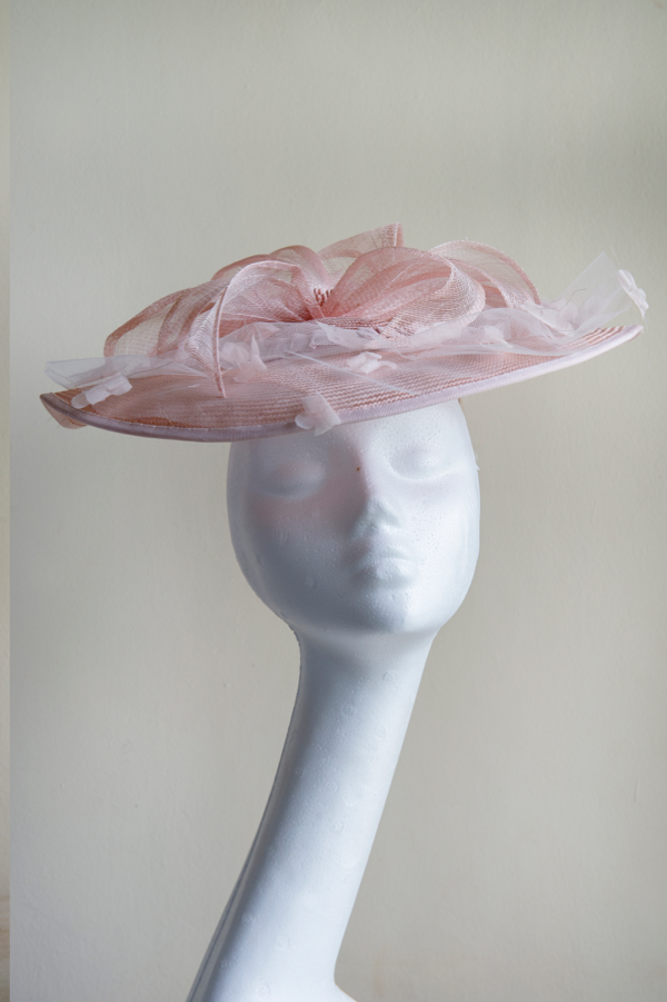 Pale pink straw hat   Trimmed with a tulle overlay, handmade organdy flowers and a large sinamay flower. This hat is very feminine and playful. It is secured to the head with an elastic.