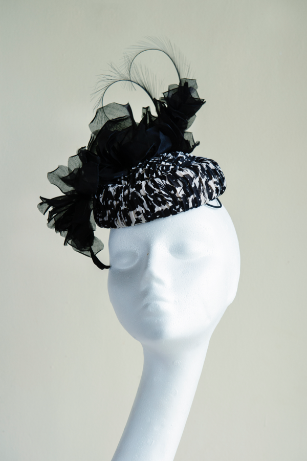 Silk Crepe Pill Box   A modern take on a classic shape. A black and white fabric pill box, with handmade organdy roses and pheasant feather curls. This hat is secured to ones head with elastic.