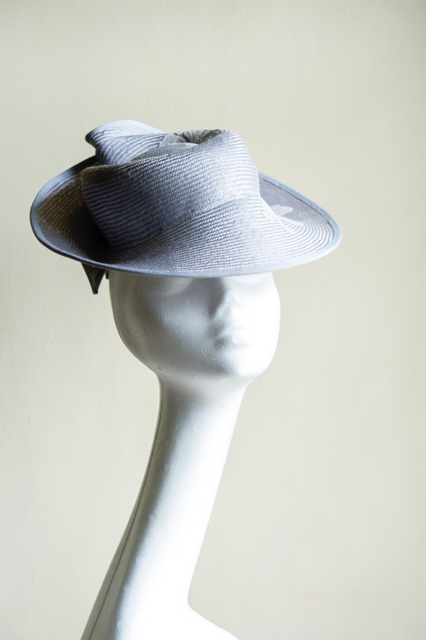Silvery blue straw percher hat   designed to perch on ones head, trimmed with vintage lace applique. A beautiful, striking and easy to wear hat. This hat is secured to ones head with elastic.
