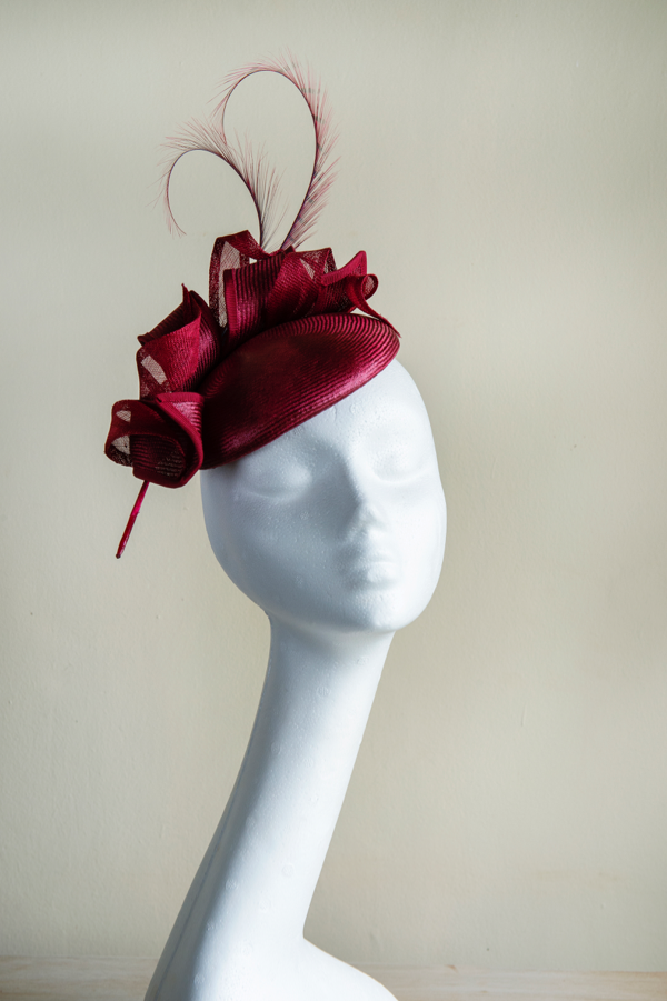Straw button hat   Trimmed with straw coils and sinamay leaves and pheasant feathers. An easy to wear shape, perfect for weddings or the races. This hat is secured to the head with an elastic.