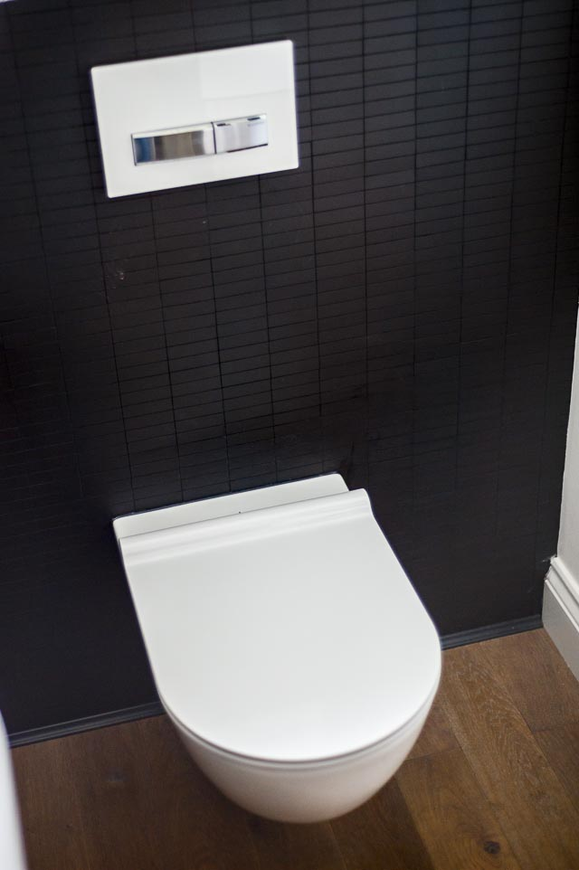 Wall Hung Toilet against Black Tiled Wall
