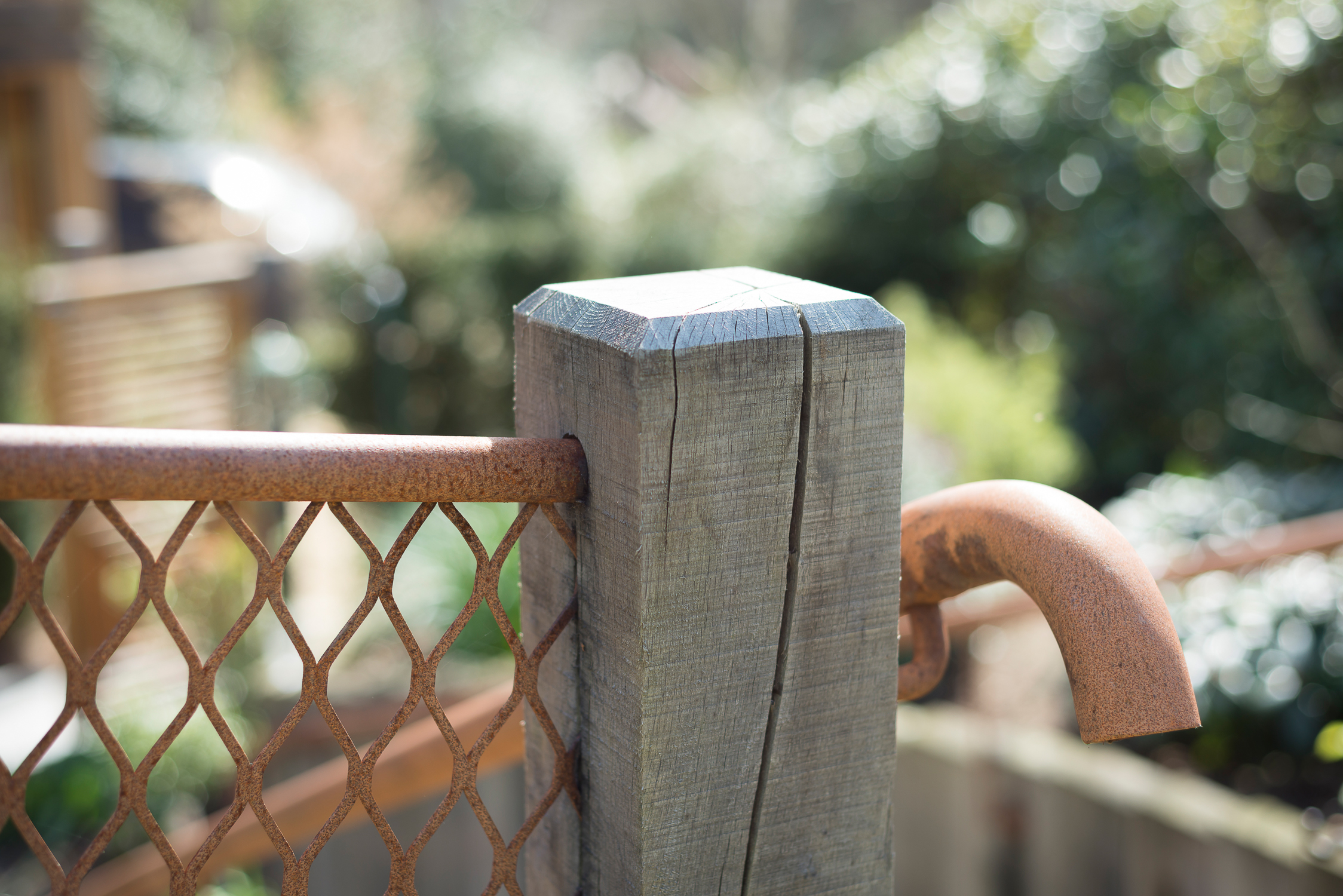 Weathered Oak Post with Rusted Mesh Fence and Hand Rail