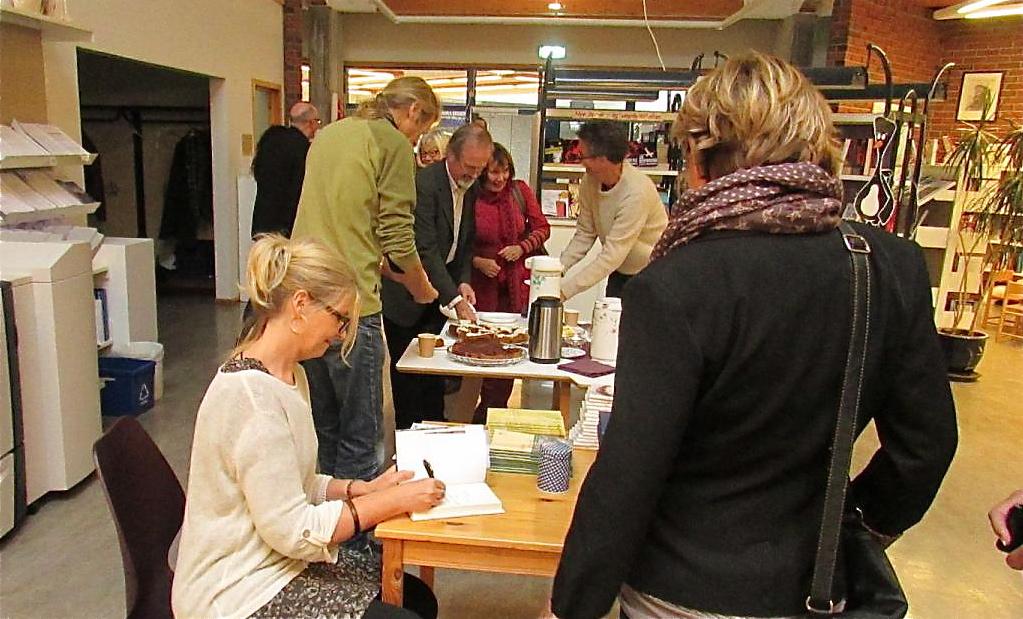 Anne Karin Fonneland signerte mange bøker under lanseringa på biblioteket laurdag. (Foto: Lars Børge Sæberg/Kvinnherad mållag)