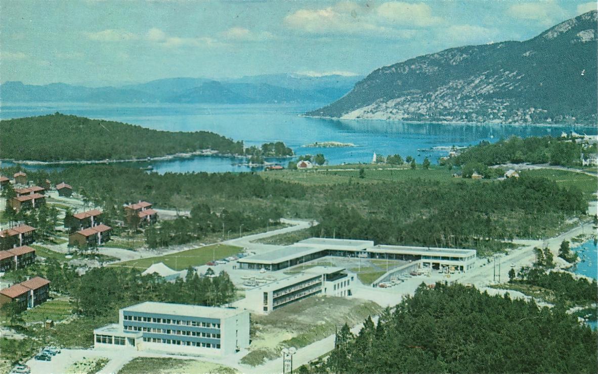 Dette biletet viser Husnes sentrum i 1970. Vi ser SØRAL sitt hybelhus, motellet og det første butikksenteret, som oslofirmaet J. B. Bakke AS bygde i 1967.