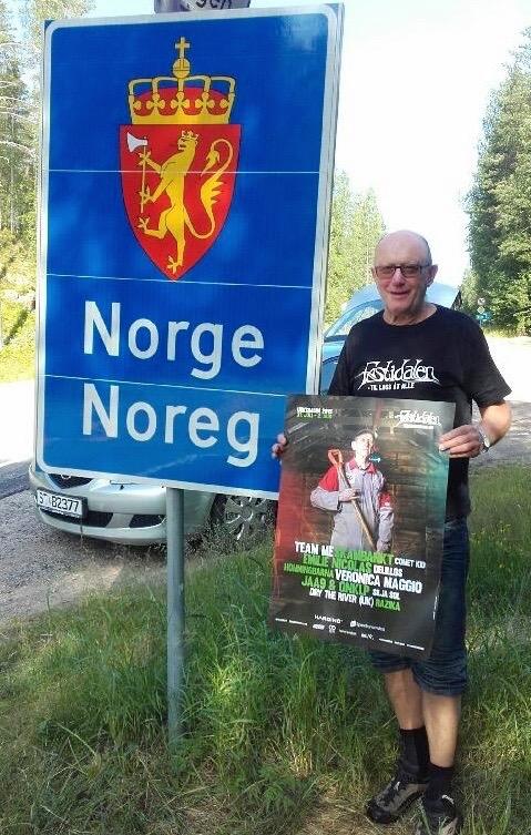Kristian Bringedal med Festidalen-plakat på riksgrensa mellom Norge og Sverige.