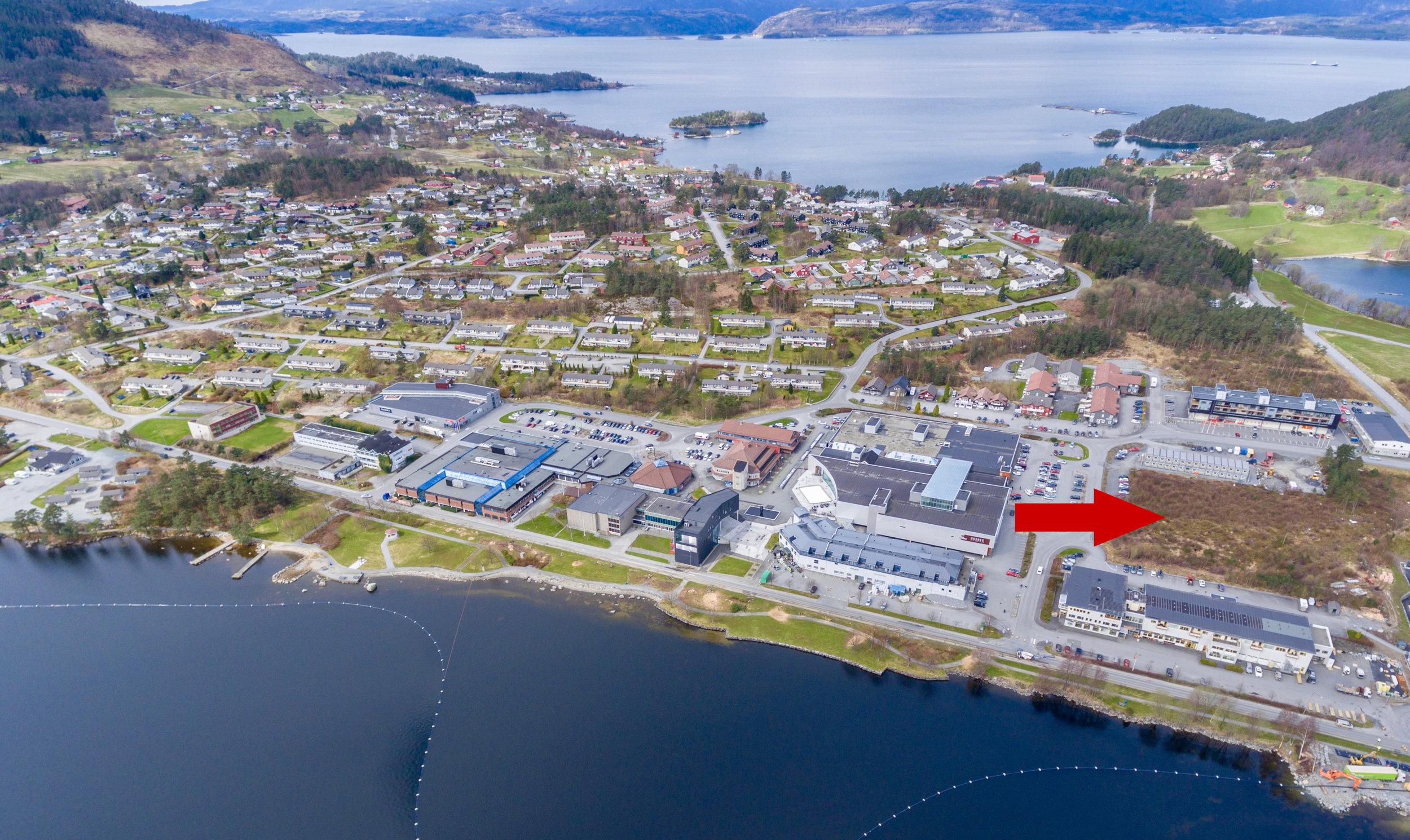 Ei av tomtene (rød pil) som vil bli diskutert i samband med planane om eit seniorsenter på Husnes. (Foto: Kvinnheringen).